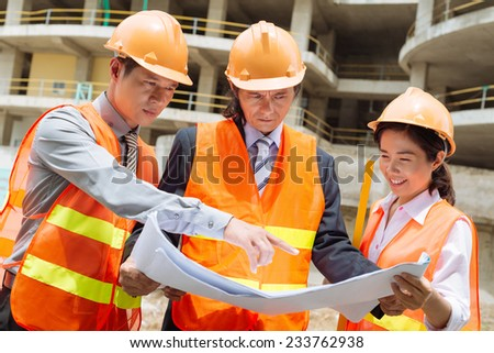 Vietnamese architects showing investor housing project - stock photo