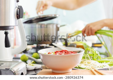 Vietnamese beef noodle soup Pho Bo with garnish of leaves of cilantro, Asian basil and bean sprouts on kitchen table. Young woman is cooking in background. Popular food in Vietnam. - stock photo