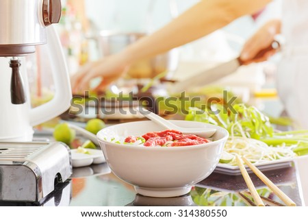 Vietnamese beef noodle soup Pho Bo with garnish of leaves of cilantro, Asian basil and bean sprouts on kitchen table. Young woman is cooking in background. Traditional healthy food. - stock photo