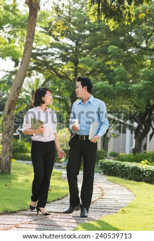 Vietnamese business couple talking while walking in the park