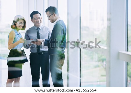 Vietnamese business executives watching something funny on tablet computer - stock photo