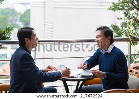 Vietnamese business partners chatting during the coffee break - stock photo