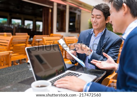 Vietnamese business partners discussing contract while sitting in the cafe - stock photo
