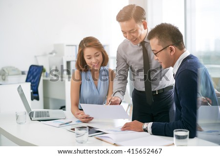 Vietnamese business team analyzing information in document