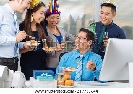 Vietnamese business team eating cupcakes at the office party - stock photo