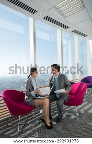 Vietnamese businessman and his pretty assistant discussing documents in modern office - stock photo