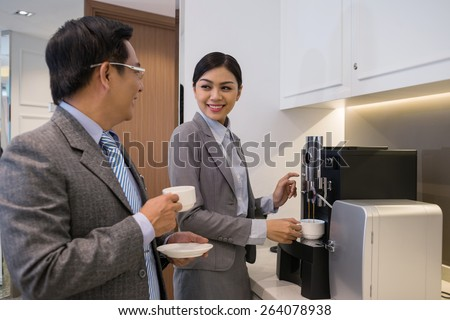 Vietnamese businessman flirting with his female colleague who is making coffee