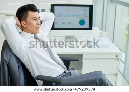 Vietnamese businessman having break and looking through window