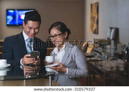 Vietnamese businessman showing funny picture or video on his smartphone to female colleague