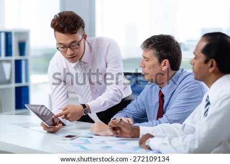 Vietnamese businessman showing information on the digital tablet to his colleagues