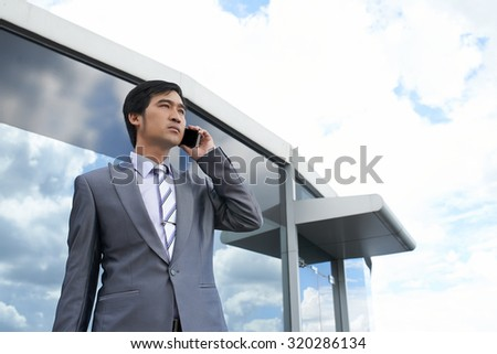 Vietnamese businessman talking on the phone and looking into distance