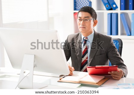 Vietnamese businessman working on computer in the office - stock photo