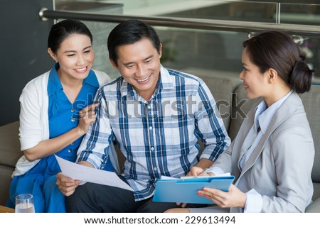 Vietnamese couple and saleswoman discussing contract - stock photo