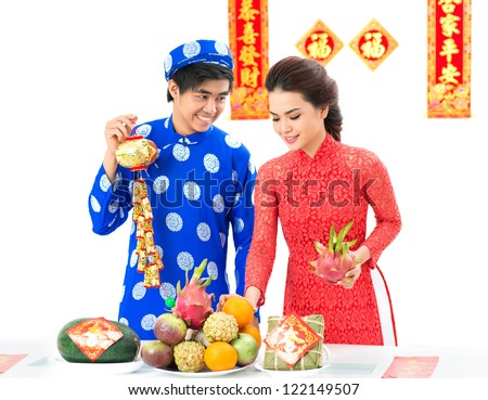 Vietnamese couple decorating festive table for Tet