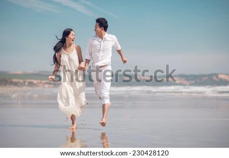 Vietnamese couple in love running on beach - stock photo