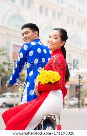 Vietnamese couple in traditional clothes cycling in the city