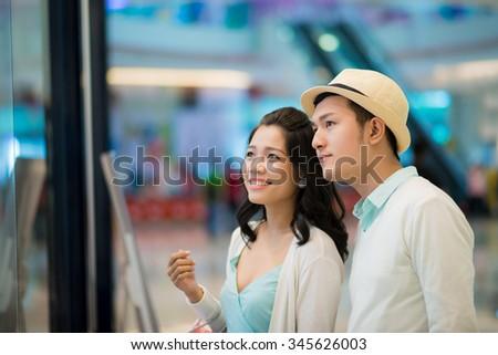 Vietnamese couple looking at showcase of boutique