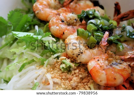 Vietnamese cuisine grilled shrimp on bed of rice noodles and greens, topped with seasoned onions. - stock photo