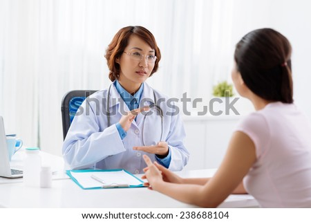 Vietnamese doctor showing something in her hands to the patient, product advertisement - stock photo
