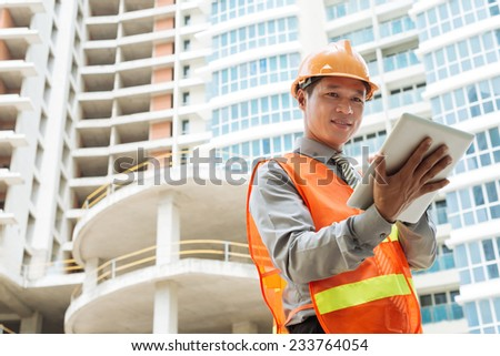 Vietnamese engineer using digital tablet at the construction site - stock photo