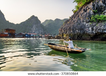 Vietnamese female in traditional boat returns to floating fishing village in the Halong Bay. The Gulf of Tonkin, the South China Sea, Vietnam. Karst towers-isles are visible in background. - stock photo