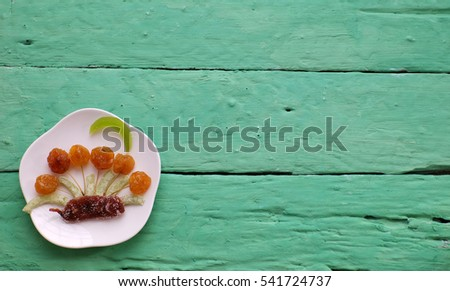 Vietnamese food for Vietnam Tet holiday, also lunar new year of Asia, colorful preserved fruit as kiwi, damson jam, or coconut jam set up on white plate with green wood background make art