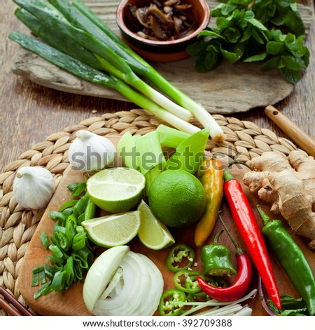 Vietnamese food ingredient board -  ginger, chili, lime, spring onion, garlic, shallots, shiitake mushroom, mint, cilantro, coriander. All colorful spices make traditional asian food more delicious.