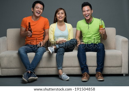 Vietnamese friends sitting on couch and watching tv - stock photo