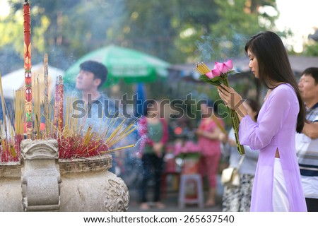Vietnamese girl praying in Buddhist temple, holding lotus flowers, Saigon, Vietnam