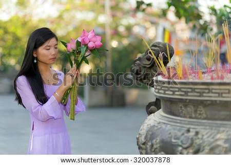 Vietnamese girl praying in Buddhist temple, holding lotus flowers, Saigon, Vietnam - stock photo
