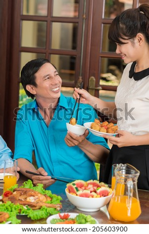 Vietnamese girl serving food to her father - stock photo
