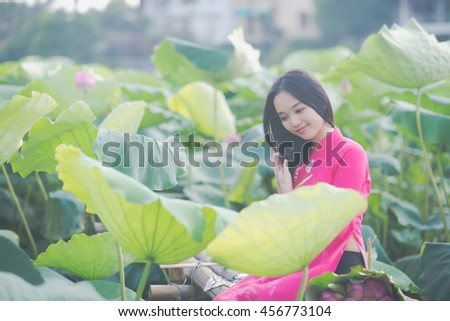 Vietnamese girl with traditional dress (ao dai) in pond of lotus flowers