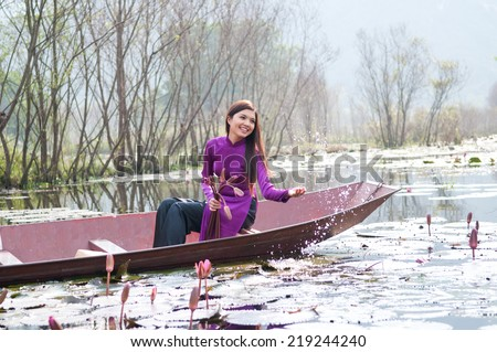 Vietnamese girl with traditional dress (ao dai) with many illy flowers in Yen stream in Hanoi.
