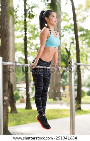 Vietnamese girl working out on gym bar - stock photo
