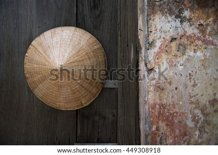 Vietnamese Hat on wooden door next to old colourful concrete wall, in Hoi An, Vietnam.  The wall perfectly for  positive copy or phases to print on with soft white screen as layer, - stock photo