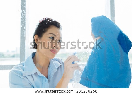 Vietnamese housewife cleaning window with spray - stock photo