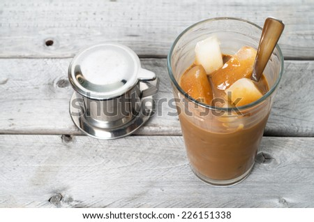 Vietnamese ice coffee with condensed milk, cafe sua da on a wooden background - stock photo