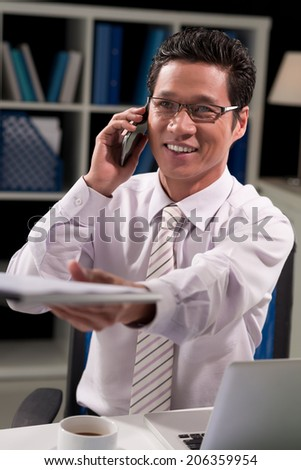 Vietnamese manager passing a document while talking on the phone - stock photo