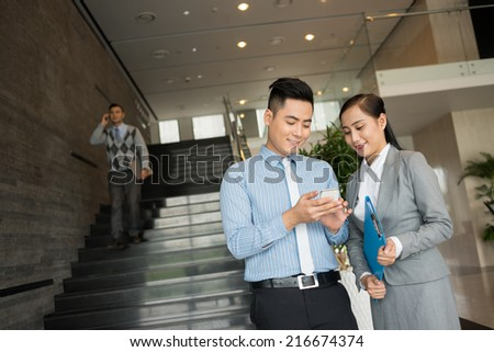 Vietnamese manager showing his female colleague some application on the smartphone - stock photo
