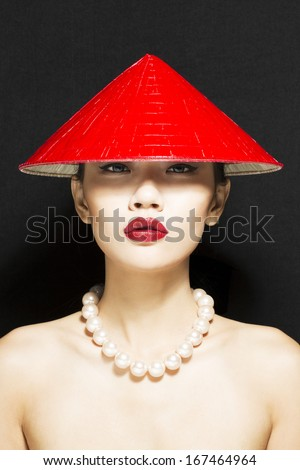 Vietnamese model wearing traditional red conical hat  - stock photo