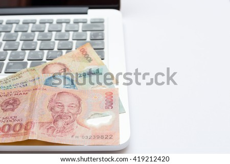 Vietnamese money on laptop, dong