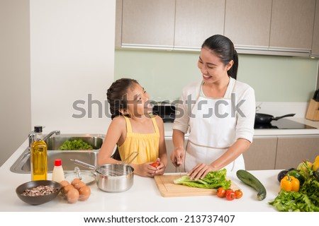 Vietnamese mother and daughter cooking together