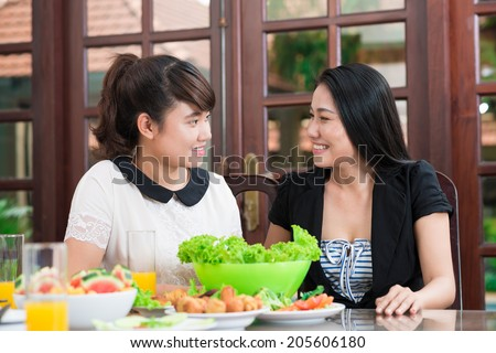 Vietnamese mother and daughter dining at home - stock photo