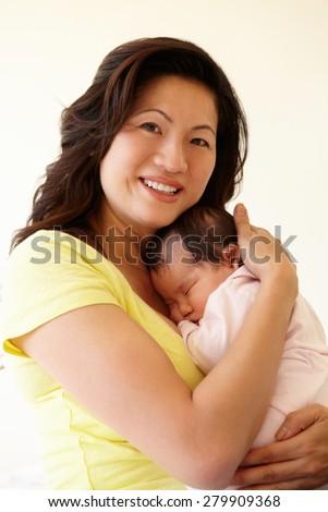Vietnamese mother cuddling baby - stock photo