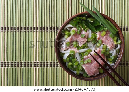 Vietnamese Pho Bo soup with beef rare, rice noodles and fresh herbs closeup. top view of a horizontal  - stock photo
