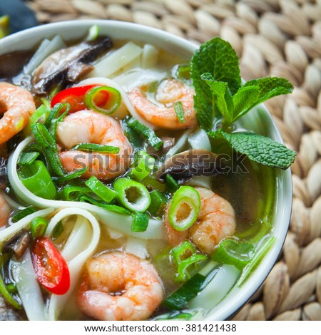 vietnamese pho tom yum -  asian soup with prawns rice noodles lime shiitake mushrooms fresh mint chilli spring onions  and sweet basil - stock photo