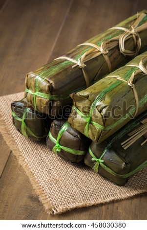 Vietnamese pork sausage steamed in banana leaf on wooden background