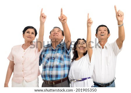 Vietnamese senior people pointing up - stock photo