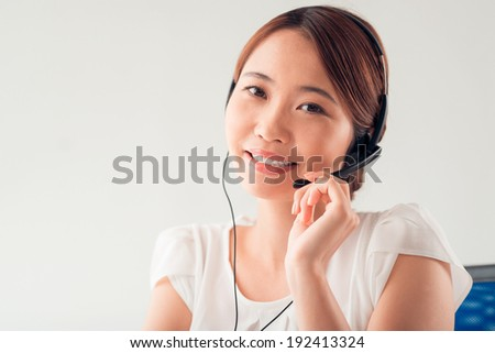 Vietnamese service worker with headset - stock photo