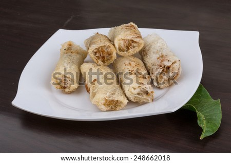 Vietnamese Spring rolls with spicy sauce on wood background